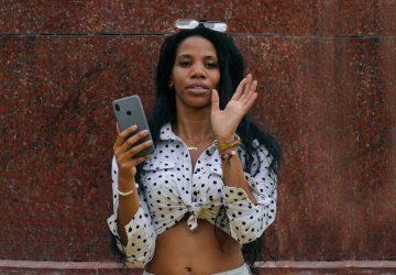 Frau im weißen und schwarzen Tupfenhemd, das silbernes iPhone hält