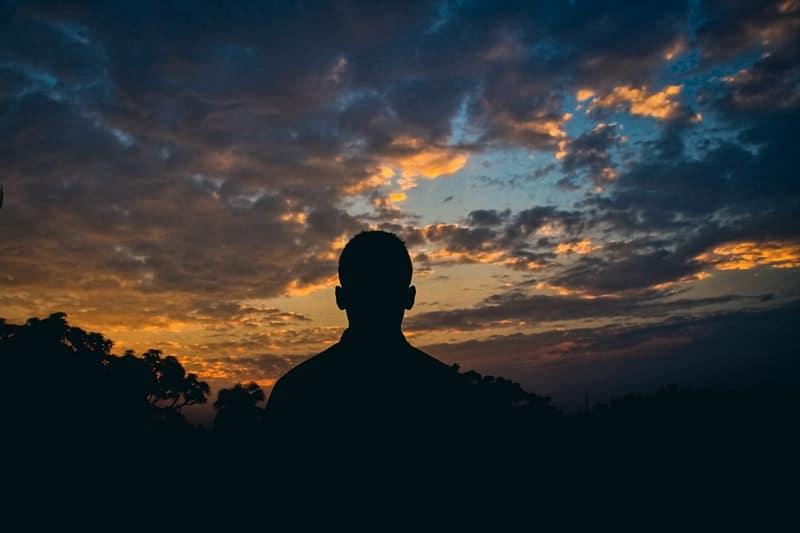 Silhouette Kerls Sonnenuntergang beobachtet