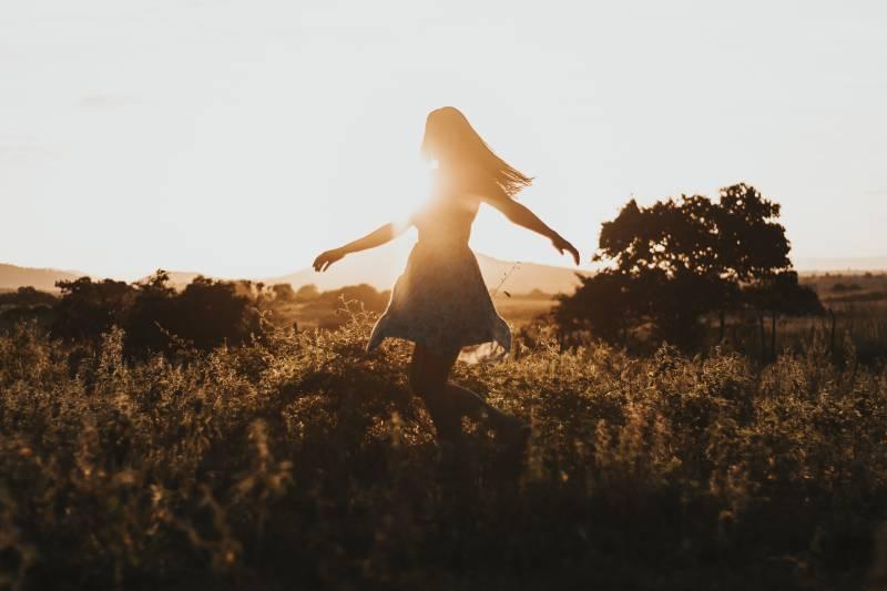 Silhouette der Frau, die in der Mitte der Wiese tanzt