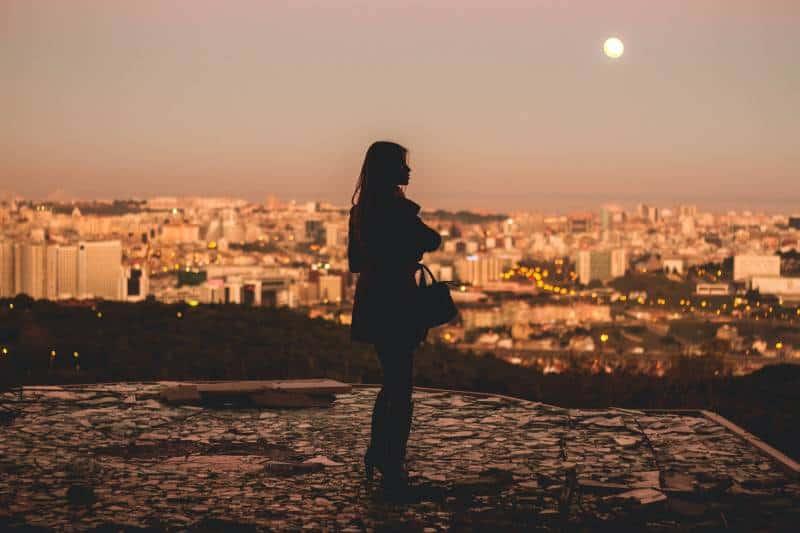 Silhouette der Frau, die während der goldenen Stunde steht