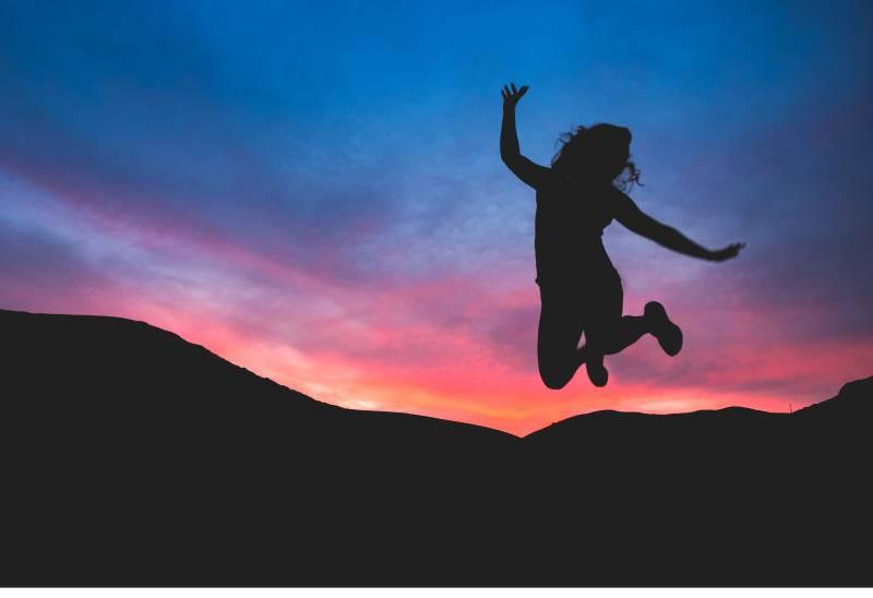 Silhouette der Person, die im Morgengrauen springt