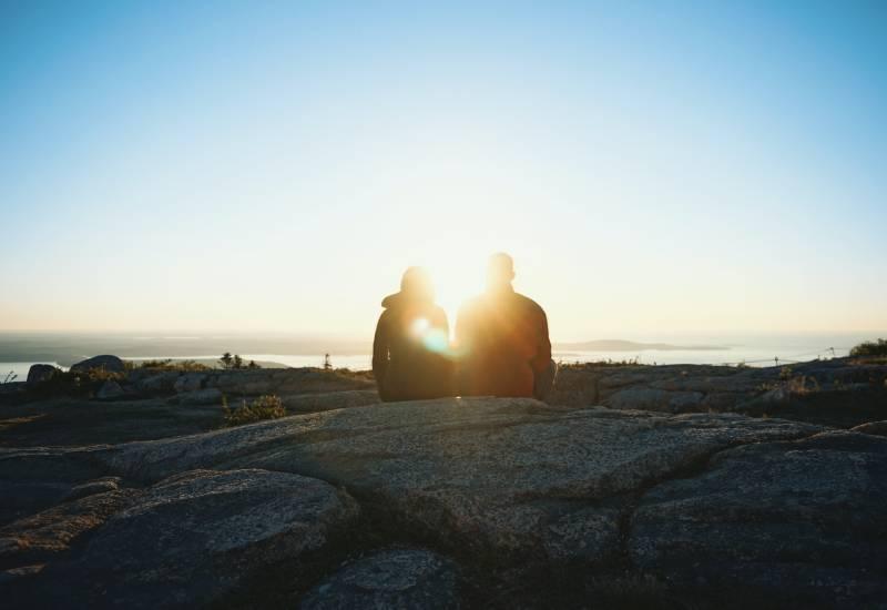 Silhouette von zwei Personen während des Sonnenaufgangs