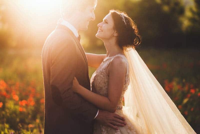 Sonnenscheinporträt der glücklichen Braut und des Bräutigams im Freien