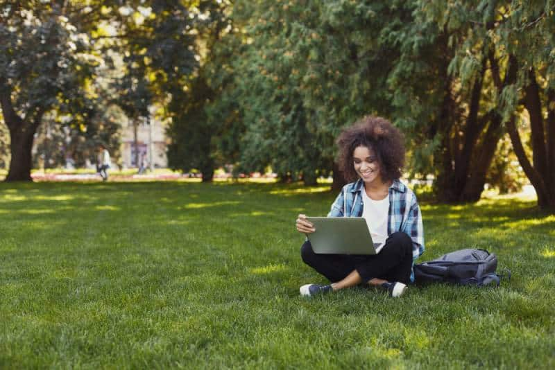 Student mit Laptop sitzt auf Gras