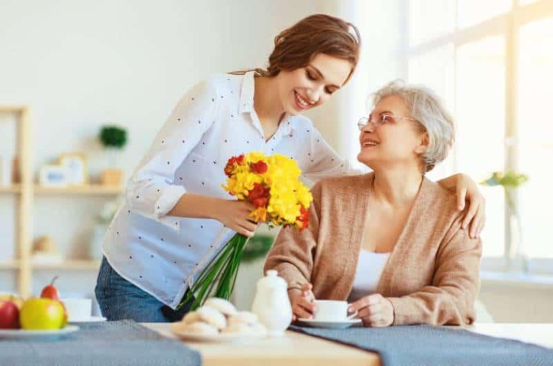 Tochter gibt ihrer Mutter zu Hause Blumen
