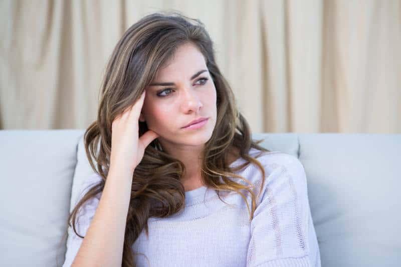 Traurige Frau, die zu Hause im Wohnzimmer wegschaut
