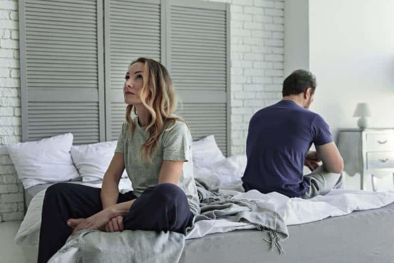 Trauriges Paar sitzt auf dem Bett