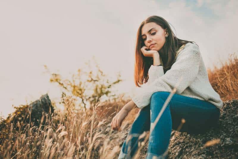 Trauriges junges Mädchen, das allein auf einem Stein draußen sitzt.