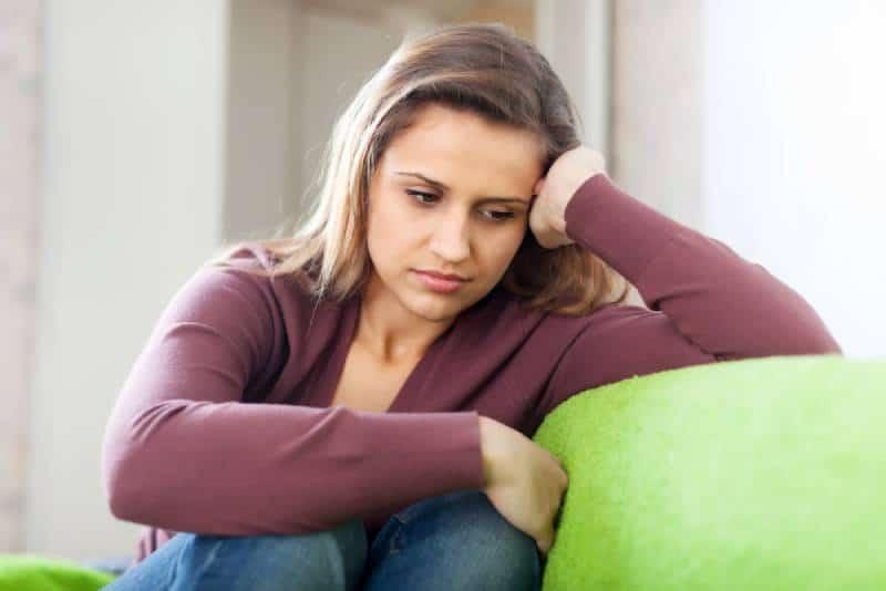 Traurigkeitsfrau, die zu Hause sitzt