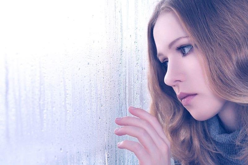 trauriges Mädchen winkt am Fenster