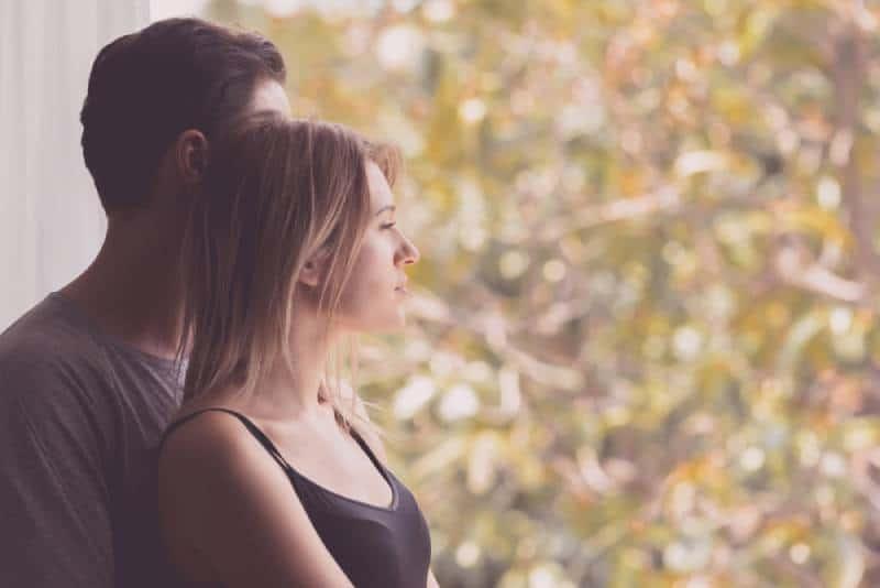 Umarmendes Paar, das draußen zu Hause Herbst schaut