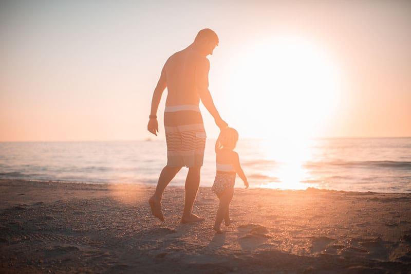 Vater geht mit seinem Kind am Strand spazieren