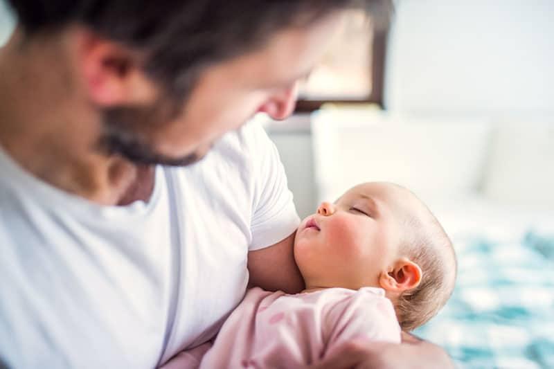Vater hält ihre kleine Tochter im Schlaf