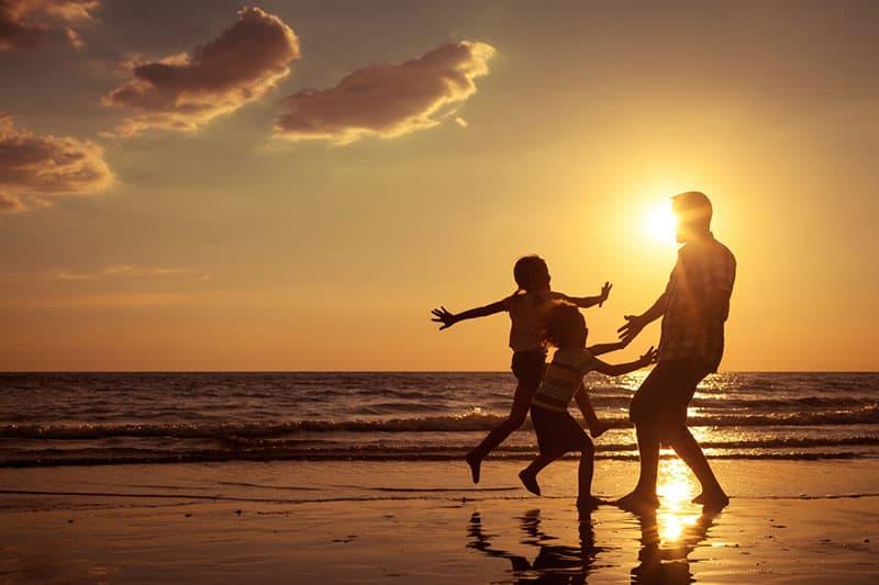 Vater spielt mit Kindern am Strand