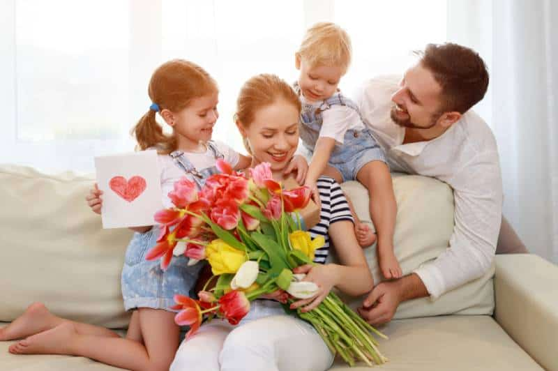 Vater und Kinder gratulieren der Mutter zum Urlaub und schenken Blumen