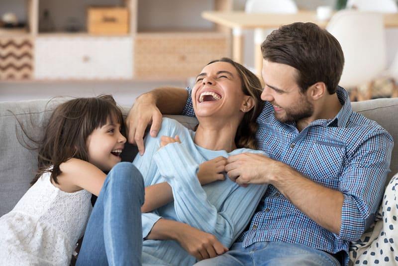 Vater und Mädchen kitzeln Mutter