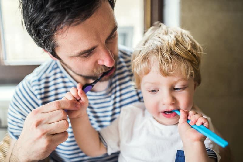 Vater und Sohn putzen sich die Zähne
