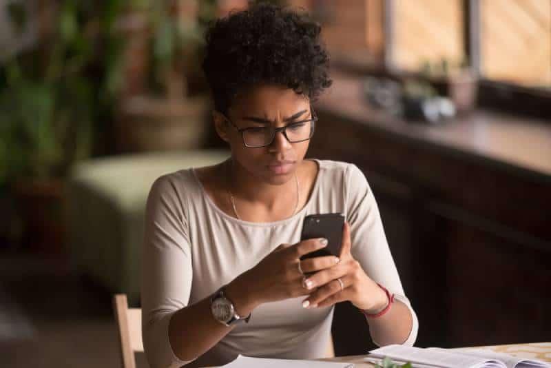Verärgerte verwirrte afrikanische Frau, die Handy hält Problem hat