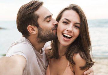 Mann küsst lächelnde Frau beim Fotografieren