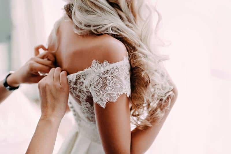 Wunderschöne, blonde Braut im weißen Luxuskleid bereitet sich auf die Hochzeit vor