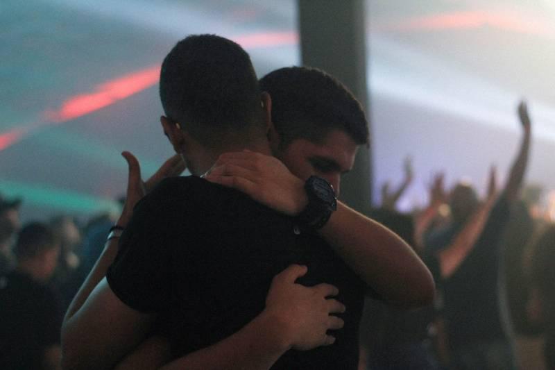 Zwei Männer umarmen sich in der Bar