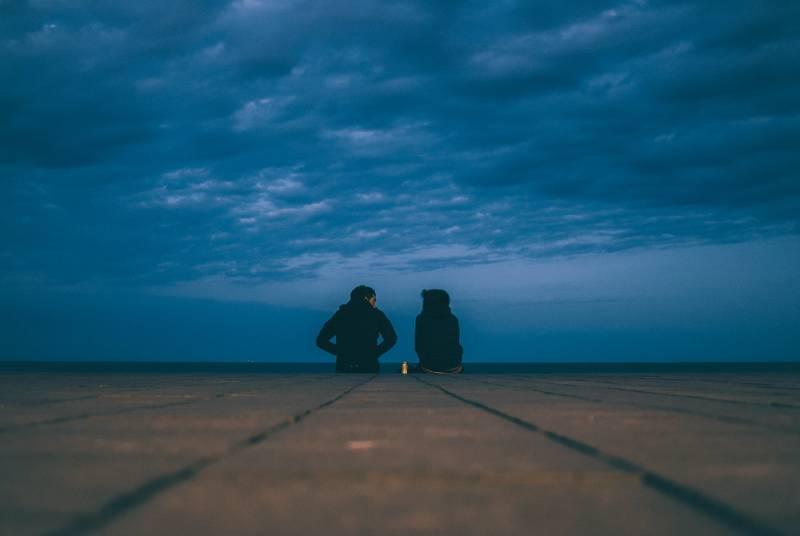 Zwei Personen tragen schwarze Jacken und sitzen auf dem Boden