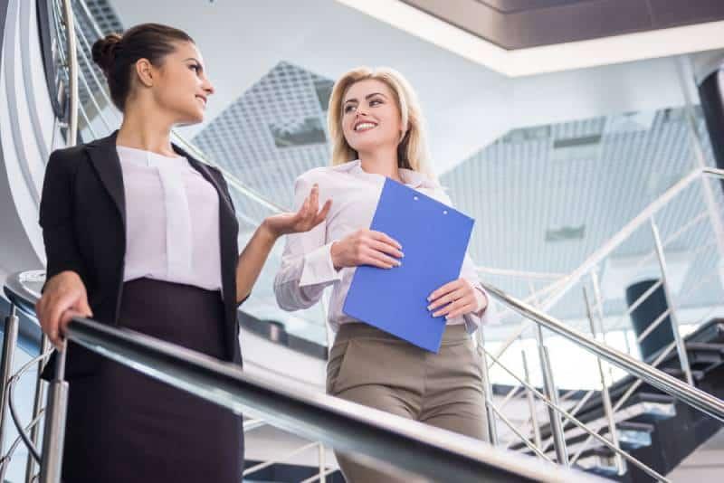 Zwei attraktive Geschäftsfrau, die die Treppe hinuntergeht und spricht.