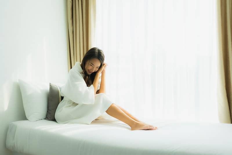 asiatische Frau, die im weißen Raum entspannt