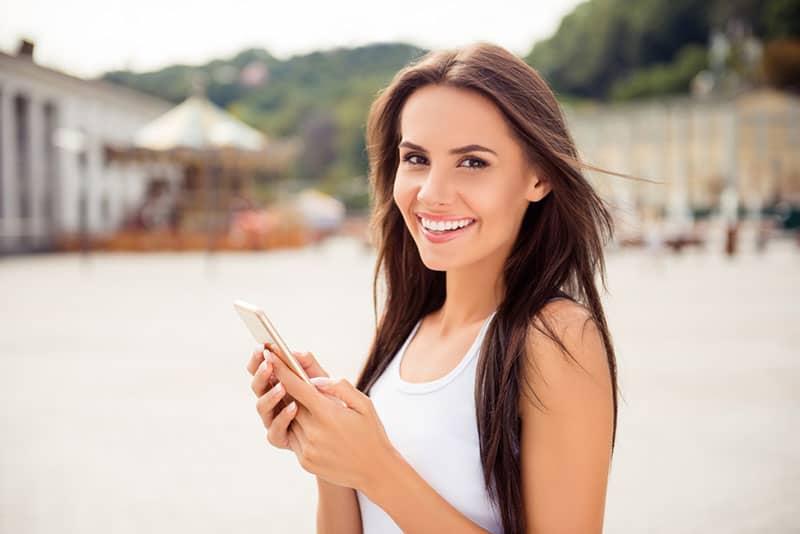 attraktive Brünette hält ein Telefon