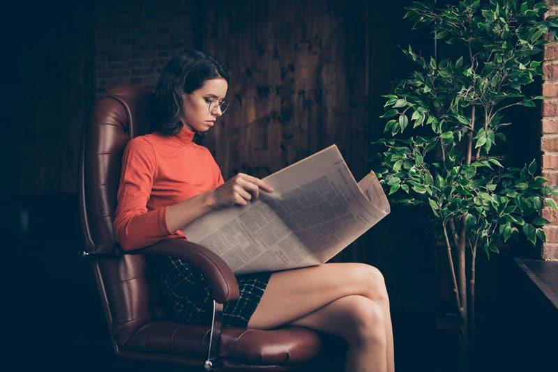 attraktive Frau, die Zeitung liest