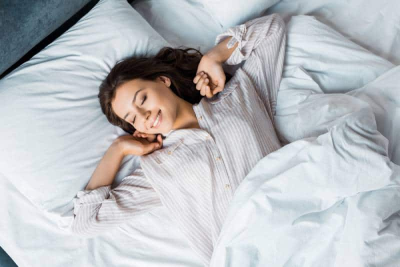 attraktive junge Frau im Pyjama, die morgens im Bett aufwacht