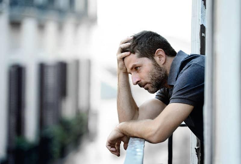 besorgter Mann auf dem Balkon stehen
