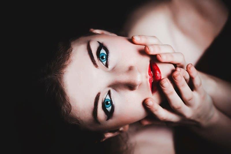 blauäugige Frau wird von ihrem Gesicht gehalten