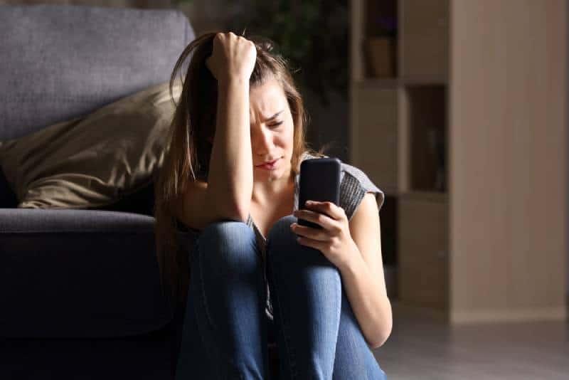 depressive Frau schaut auf ihr Handy