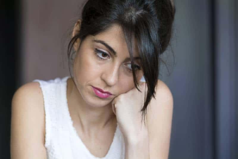 depressive junge Frau, die sich zu Hause an die Hand lehnt