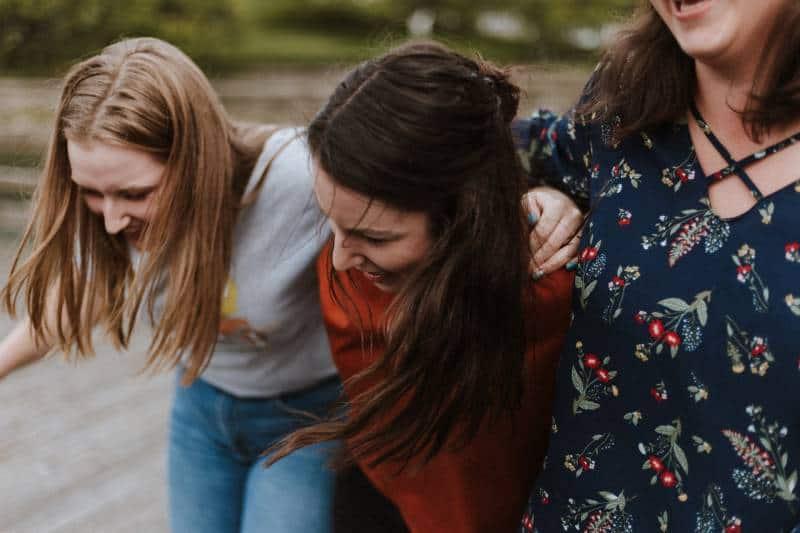 drei Frauen halten sich draußen fest