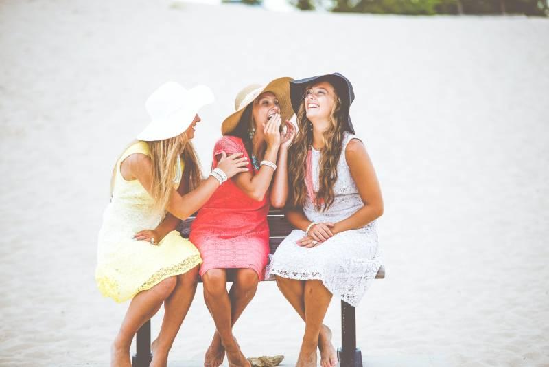 drei Frauen sitzen auf brauner Holzbank