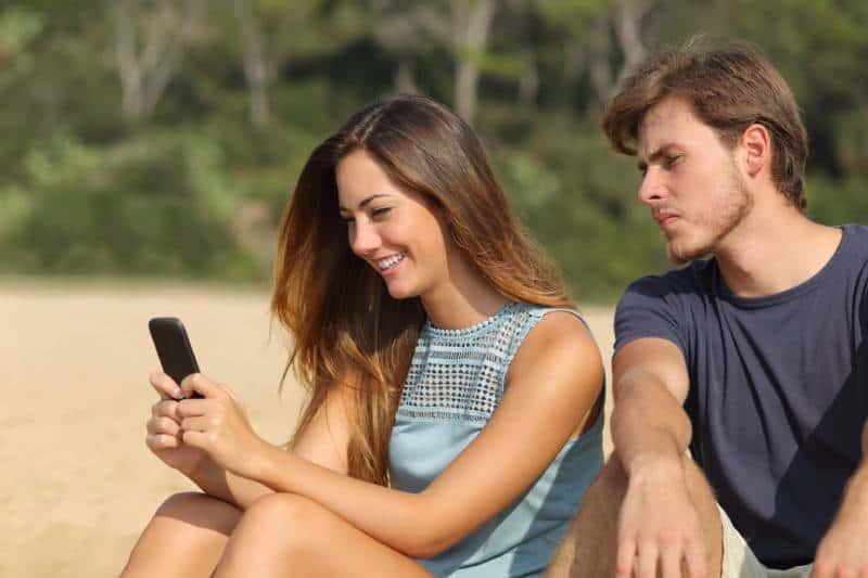 eifersüchtiger Mann, der draußen auf das Telefon der Frau schaut