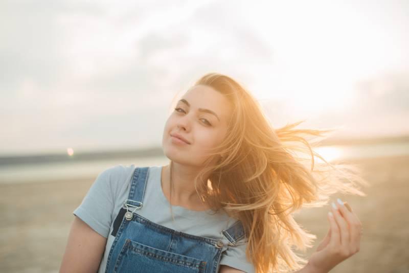 ein Mädchen mit großen blauen Augen, der Wind weht ihr Haar, Sonnenuntergang