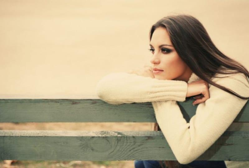 ein-junges-einsames-Mädchen-das-auf-einer-Parkbank-sitzt