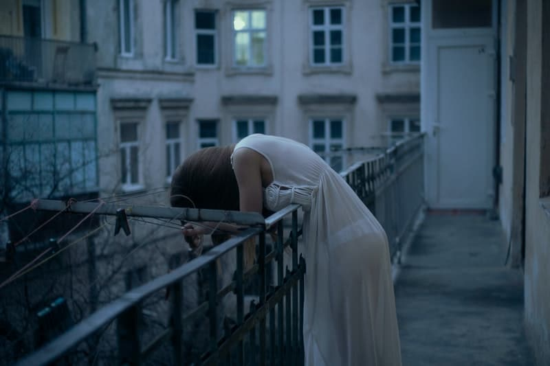 eine Frau, die sich über einen Zaun beugt