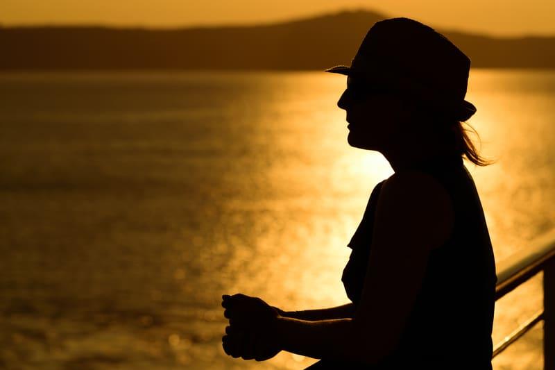 eine Frau mit einem Hut bei Sonnenuntergang