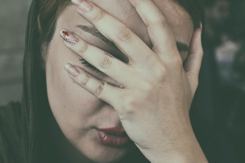 eine Frau mit einer Hand im Gesicht