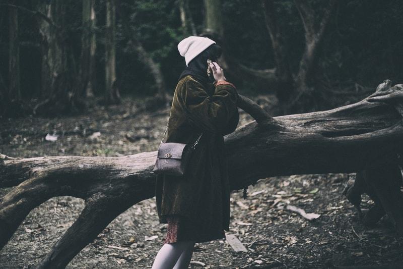 eine Frau neben einem großen Baum im Wald