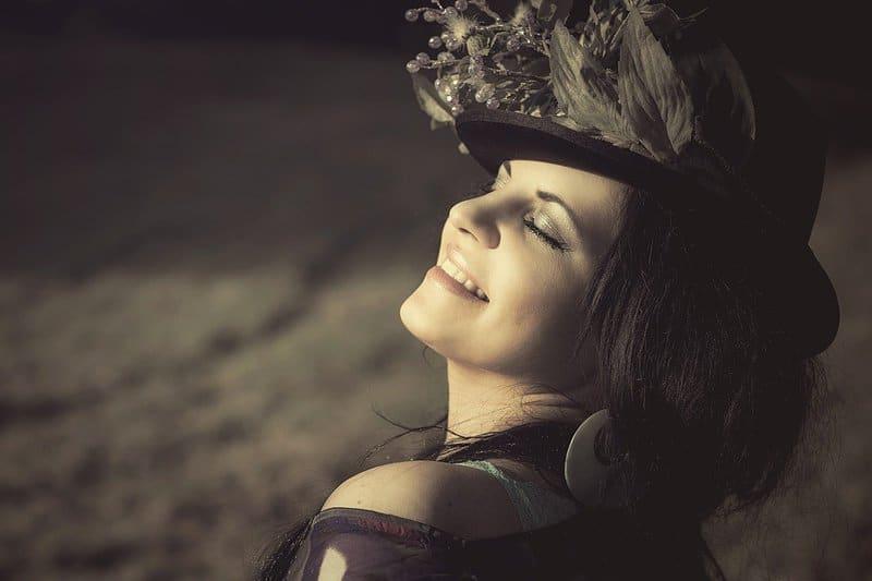 eine zufriedene Frau in der Sonne mit Hut