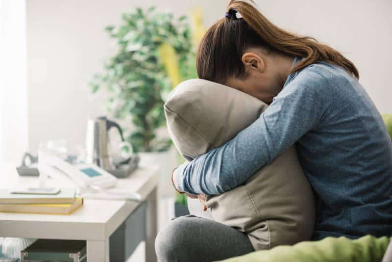 einsame Frau zu Hause versteckt ihr Gesicht auf einem Kissen