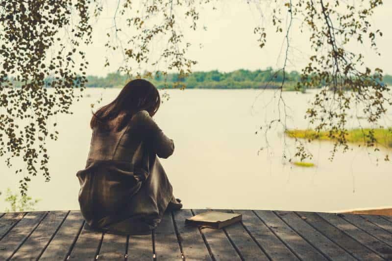 einsames Mädchen, das auf Holz am See sitzt