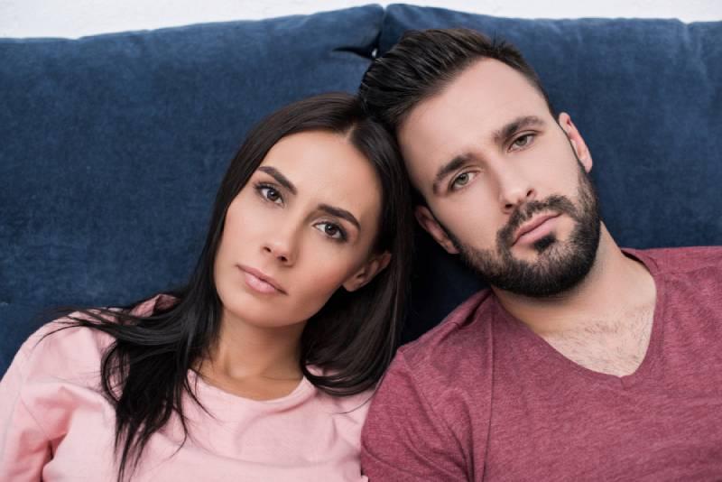 emotionsloses junges Paar, das sich aneinander lehnt, während es auf der Couch sitzt