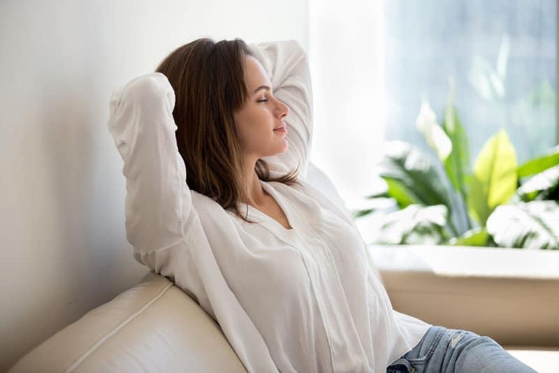 entspannte Frau sitzt auf der Couch