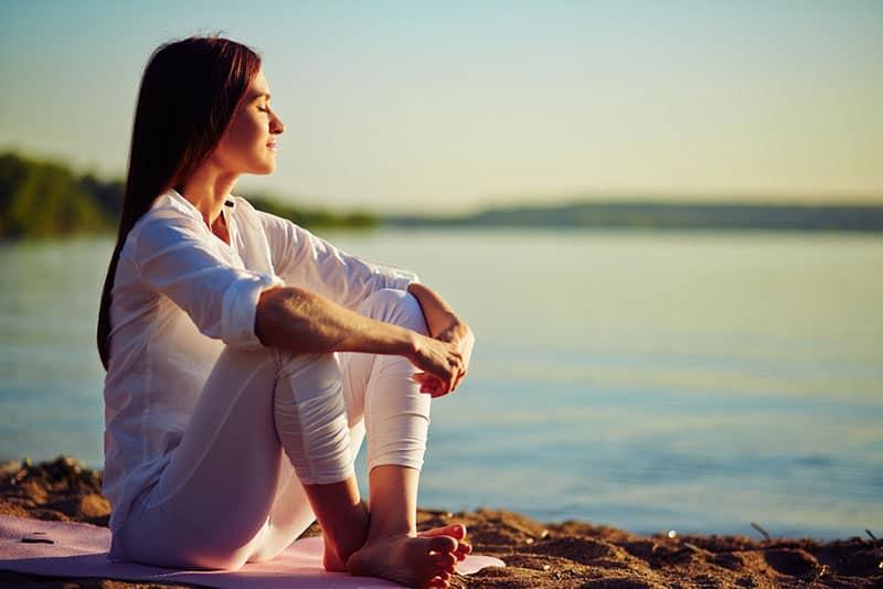 entspannte Frau sitzt im Sand